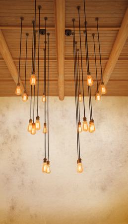 home decorated: ceiling light bulb hanging on pine wood against warm tone of grungy cement wall use as home decorated background,backdrop and copy space