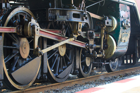 railway history: iron wheels of stream engine locomotive train on railways track perspective to golden light forward use for old and classic period land transport and retro vintage style background