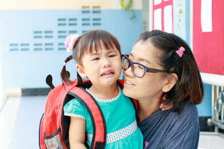 holding back: children and mother crying first day go to pre-kindergarten school Stock Photo