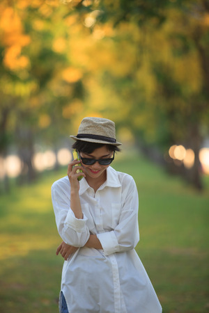 communicated: beautiful young woman wearing sun glassea nd straw hat talking on mobile phone with happiness emotion against blurry yellow flower in park use for people and modern life in digital connecting technology Stock Photo