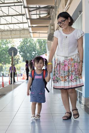 maestra preescolar: hijos y su madre van a la escuela el primer uso día para la educación, niño en el jardín de infantes Foto de archivo