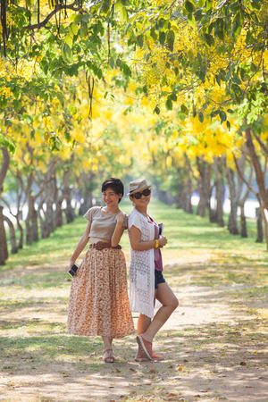 happieness: portrait of couples beautiful asian woman standing in blooming flowers park with happieness emotion