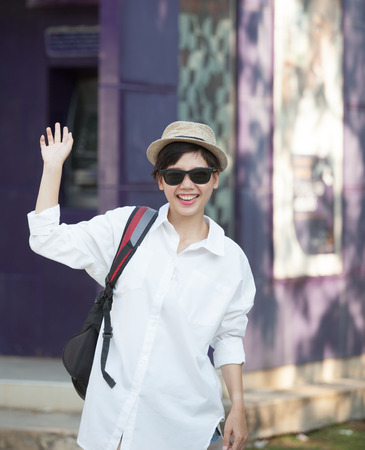 hi hat: portrait of young woman wearing sun glasses and straw hat relaxing emotion with hipster looking and say hi greeting to people on side road scene Stock Photo