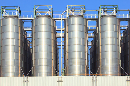 energy use: metal steel tank storage in heavy industry estate plant against clear blue sky use for industrial and factory manufacting of oil fuel and fossil energy background,backdrop Stock Photo