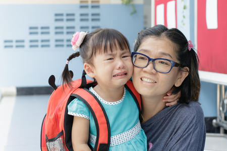 first day of school: children and mother crying first day go to pre-kindergarten school Stock Photo