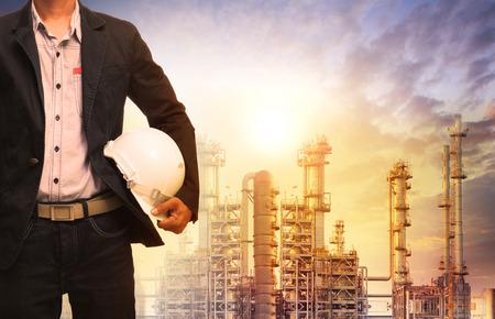 techniek man met witte veiligheidshelm staande voor olieraffinaderij bouwwerk in de zware petrochemische industrie