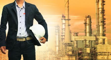 techniek man en helm staande tegen olieraffinaderij in de zware petrochemische industrieterrein