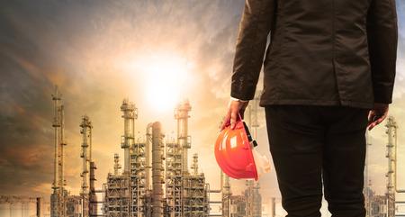 Engineering-Mann mit Schutzhelm stehend in der Industrie Immobilien gegen Sonnenaufgang über Raffinerie-Anlage