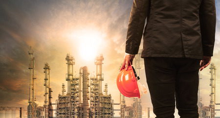 engineering man with safety helmet standing in industry estate against sun rising above oil refinery plant