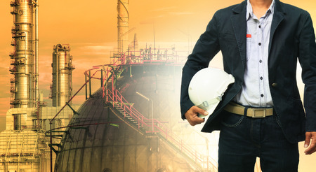 Ingenieurmann und Schutzhelm stehend gegen Öl-Raffinerie-Anlage in schweren petrochemischen Industriepark