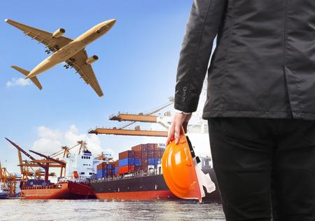 Arbeiter und Handelsschiff am Hafen und Luftfrachtflugzeug fliegt über den Einsatz für Wasser-und Luftverkehr, Logistik Import-Export-Industrie