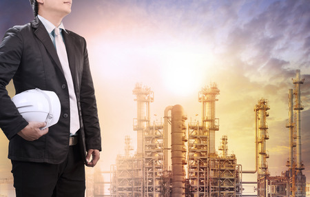 industries: engineering man with safety helmet standing against oil refinery plant in heavy petrochemical industry estate use for fossil energy and petroleum power topic