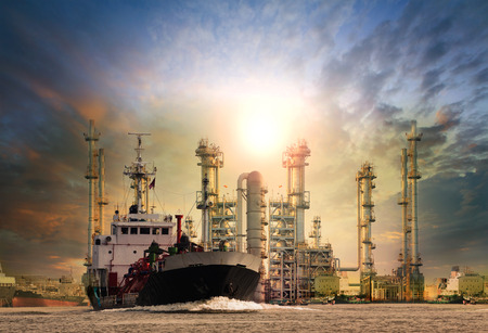 gas tanker ship and oil refinery plant background use for oil fuel energy and fossil power .transportation and heavy petroleum industry estate theme