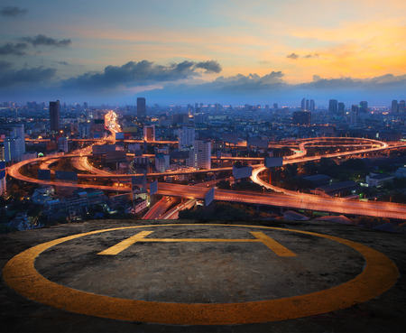 helicopter pad on top building roof against beautiful express way and land transportation in dusky sky city scape