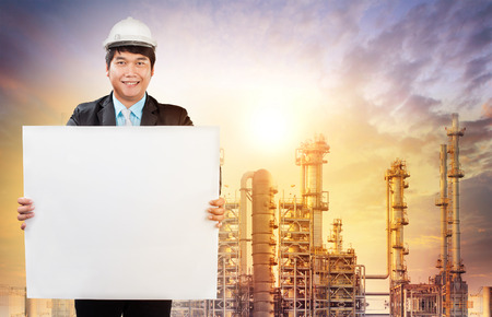 annoucement: engineering man with white empty white broad standing in front of oil refinery industry estate use for industrial theme
