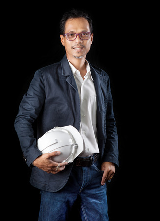 45 years old: portrait of smiling face 45 years old asian working man in construction industry holding safety helmet standing against black background use for people occupation theme Stock Photo