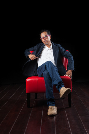45 years old: portrait of 45 years old asian man sitting on red sofa against black background Stock Photo
