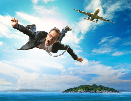 flying man: business man flying from passenger plane over natural blue ocean island use for people holiday and vacation time to relaxing destination Stock Photo