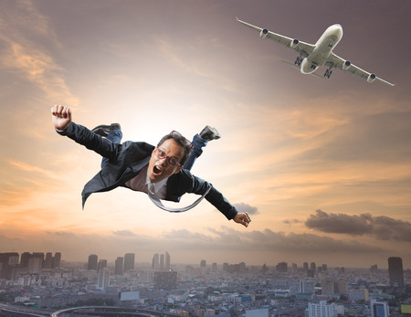 flying man: crazy business man flying from passenger plane with glad and happiness emotion use for new trend ,  people traveling ,and top secret strategy