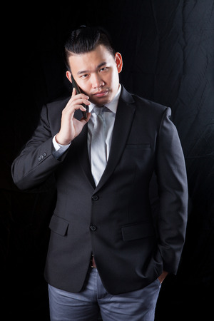 communicated: young asian business man talking on mobile phone against black background  with studio lighting
