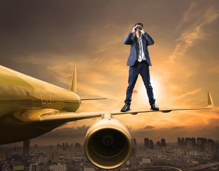 ビジネスの男性と双眼鏡レンズの演技使用商業競争とトップの秘密の戦略のためのスパイ飛行機の翼上に立っています。