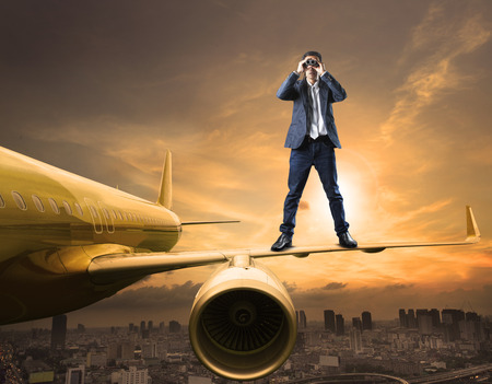 Business-Mann und ein Fernglas Objektiv steht auf Flugzeug Flügel Spionage handeln Nutzung für kommerzielle Konkurrenz und streng geheimen Strategie Lizenzfreie Bilder