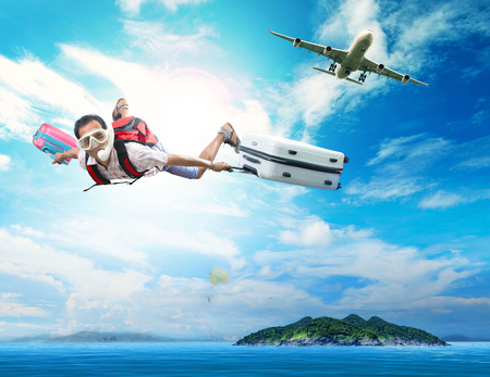 young man flying on blue sky wearing snorkeling mask and holding luggage use for people traveling by plane to destination sea island and summer vacation holiday theme Foto de archivo