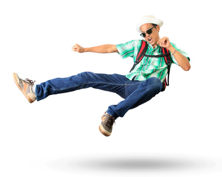 back pack: young man with back pack sky kick jumping action isolated white background Stock Photo