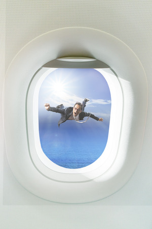 plane window: business man floating mid air out side passenger plane window