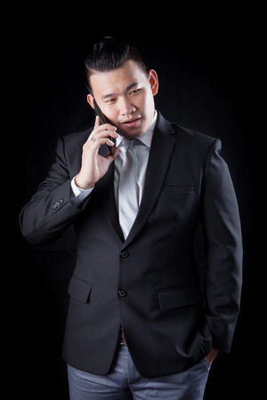 communicated: portrait of asian business man talking mobile phone against blac background photography by low key light technique in studio