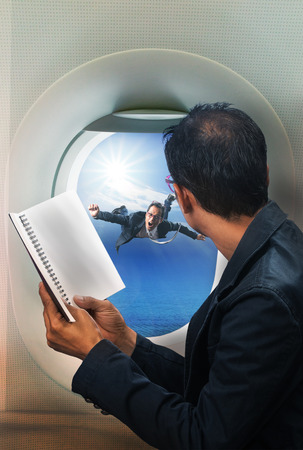 follow through: business man reading book in passenger plane seat and looking to out side of plane see another buseness man flying beside a window