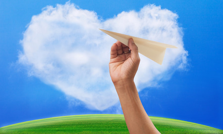 infomation: hand preparing to throwing paper plane to mid air againt green grass field and heart shape white clouds on clear blue sky Stock Photo