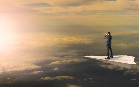 business man standing and spying binocular on papet plane against sun rising over cloud scape