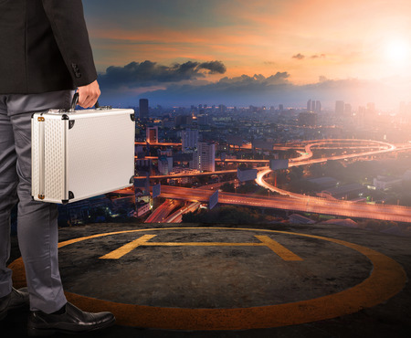 helicopter pad: business man with strong metal breifcase standing on helicopter pad on top of building roof with sun rising over urban scene