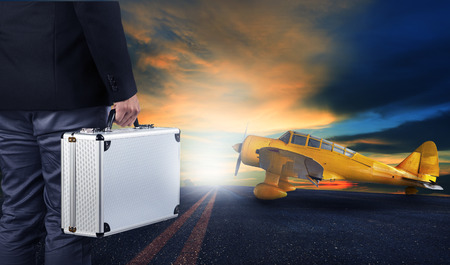 runways: business man with metal strong luggage standing in airport runways with yellow old yellow propeller plane use for air transport and people traveling theme,concept,conception,conceptual,