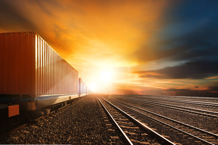 goods train: industry container trains running on railways track against beautiful sun set sky use for land transport and logistic business