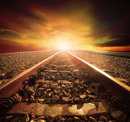 travel industry: junction of railways track in trains station agains beautiful light of sun set sky use for land transport and logistic industry background ,backdrop,copy space theme