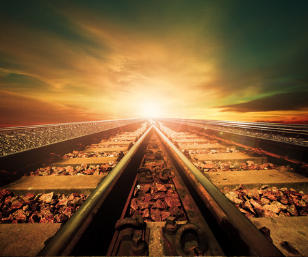 railroad transportation: junction of railways track in trains station agains beautiful light of sun set sky use for land transport and logistic industry background ,backdrop,copy space theme