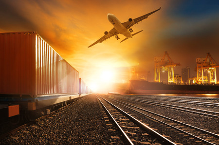 container port: industry container trainst running on railways track and commercial ship in port ,plane air cargo flying above  use for land ,air ,and vessel transport industry  and logistic business