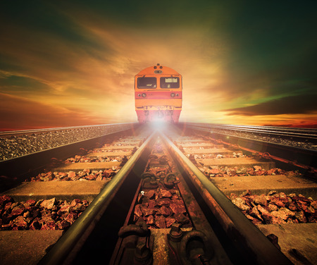 trains on junction of railways track in trains station agains beautiful light of sun set sky use for land transport and logistic industry background ,backdrop,copy space theme