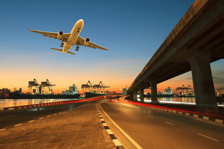 and the air: road ,land bridge run into ship port and commercial cargo plane flying above use for land ,air and vessel transport industry business Stock Photo
