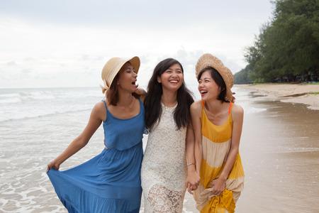 Porträt der jungen asiatischen Frau mit Glück Emotion tragen schönes Kleid zu Fuß auf Meer Strand und lachen fröhlich Einsatz für Menschen, erholsamen Urlaub an der Ziel