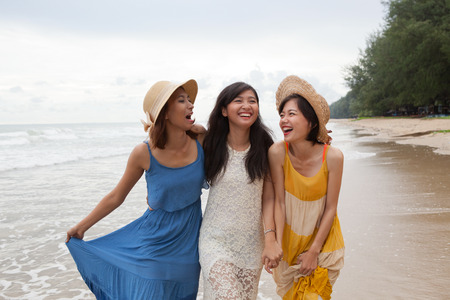 portrait of young asian woman with happiness emotion wearing beautiful dress walking on sea beach and laughing joyful use for people relaxing vacation on destination Stock Photo