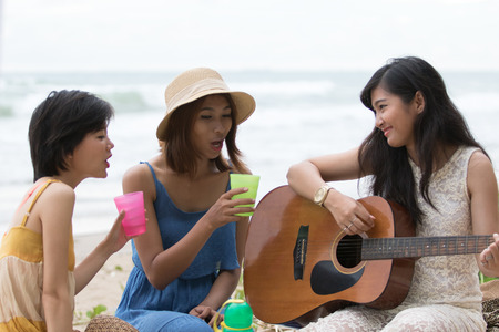 portrait of asian woman and friends group playing guitar and happiness singing a song use for people relaxing holiday at sea side photo