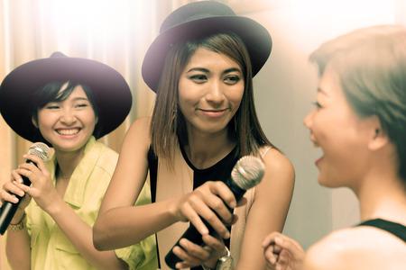 幸福の感情とうれしそうな幸せそうな顔で caraoke エンターテイメント ルームで歌を歌っているアジアの若い女性の肖像画のグループ 写真素材