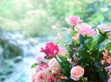 녹색 흐림 배경에 대해 인공 장미 꽃 꽃다발 배열