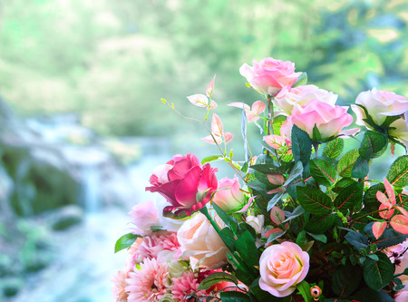 artificial roses flowers bouquet arrangement against green blur background Stock Photo
