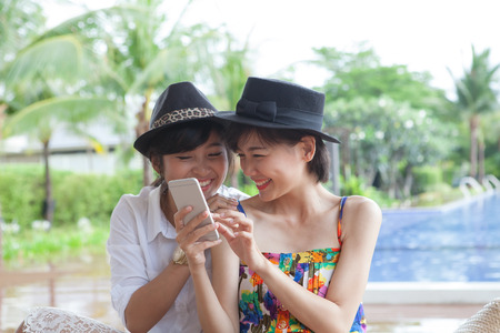 portrait of young beautiful asian woman laughing with happiness face looking to smart phone use for people and digital modern life connecting on line by mobile phone chat 版權商用圖片