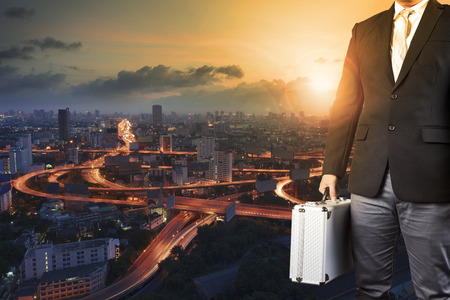 manage transportation: business man and metal briefcase luggage in hand standing against express way of capital town and sun rising sky Stock Photo