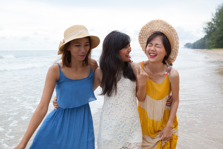 joy: portrait of young asian woman with happiness emotion wearing beautiful dress walking on sea beach and laughing joyful use for people relaxing vacation on destination Stock Photo